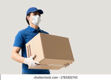 Young delivery man wearing face mask and gloves while carrying cardboard box during coronavirus outbreak