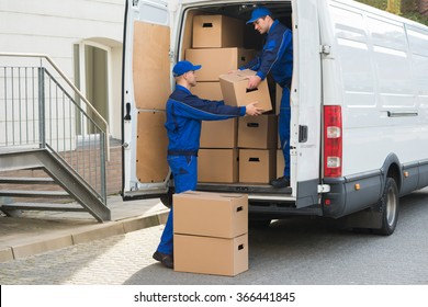 Young delivery men unloading cardboard boxes from truck