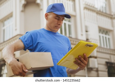 Young deliveryman checking adress of a client on his clipboard, carrying cardboard box parcel. Handsome postman in blue uniform delivering package