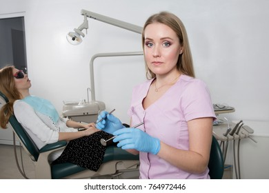 Young dental doctor girl holding a medical instrument against the background of a dental office. In the chair sits a patient