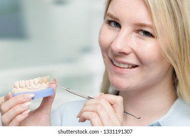 Young dental technician works on tooth crown in dental laboratory