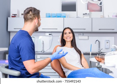 A young Dentist consulting a female Patient in the dental studio before treatment.