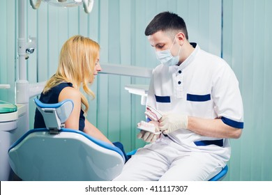 Young dentist explaining how to care of teeth to female patient