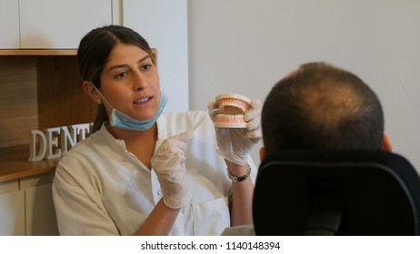 Young dentist explains about mouth hygeen to a patient