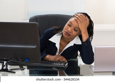 Young Depressed Businesswoman Sitting At Office Desk