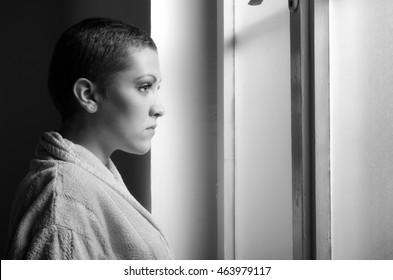 Young depressed cancer patient standing in front of hospital window in black and white.