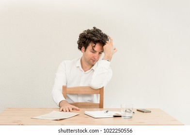 Young depressed Caucasian freelancer man sitting in his home office at the table in front of empty clear wall.