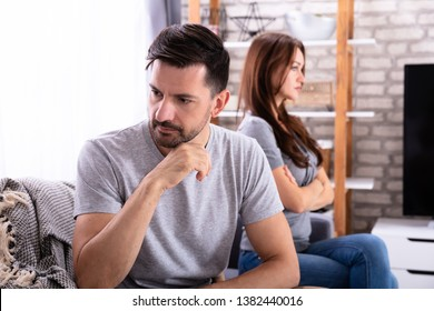 Young Depressed Couple Sitting On Sofa At Home