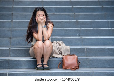 young depressed and desperate Asian Chinese business woman crying alone sitting on street staircase suffering stress and depression crisis being victim of mobbing or fired losing her job
