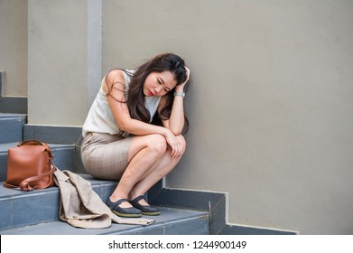 young depressed and desperate Asian Japanese business woman crying alone sitting on street staircase suffering stress and depression crisis being victim of mobbing or fired losing her job
