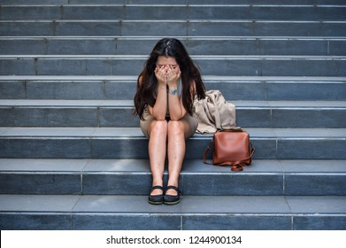 young depressed and desperate Asian Korean businesswoman crying alone sitting on street staircase suffering stress and depression crisis being victim of mobbing or fired losing her job