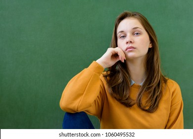 Young depressed female high school student sitting in front of chalkboard in classroom, with her hand on chin. Waist up portrait.