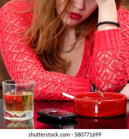Young depressed girl drinking alcohol and smoking at home while waiting for important phone call.