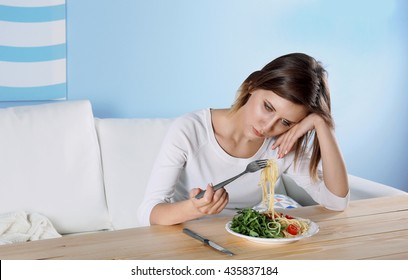 Young depressed girl with eating disorder at wooden table