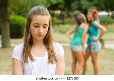 Young depressed girl rejected by other teenage girls standing in park on beautiful summer day.