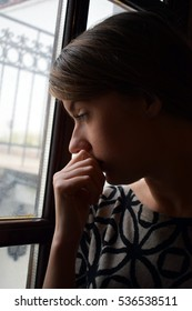 Young depressed girl is thinking and looking out the window.She is sad.