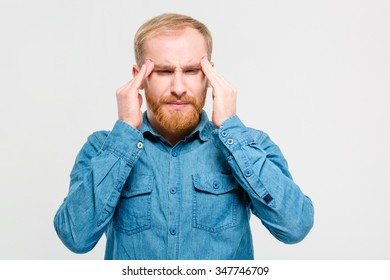 Young depressed handsome bearded man in jeans shirt touching his temples and having a headache over white background