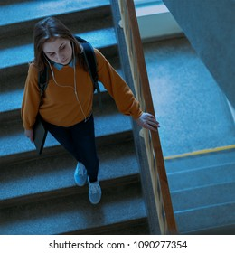 Young depressed lonely female college student walking down the stairs at her school, looking down. Education, Bullying, Depression concept.