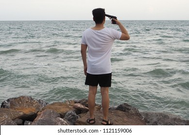 Young depressed man committing suicide using gun shooting his head on the beach. Violence and stress concept