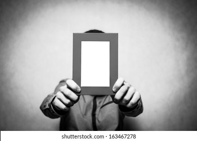 A young depressed man holding the picture frame, black&white