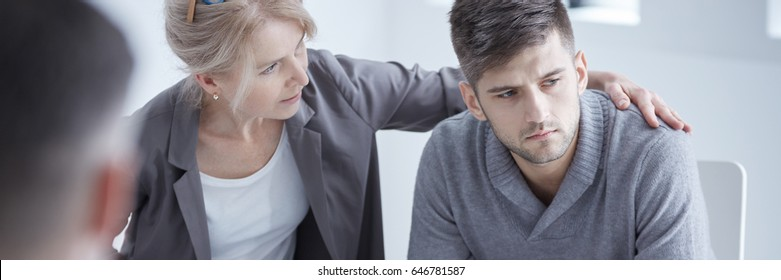 Young depressed young man in mourning talking with grief counselor