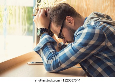 Young depressed man sitting at table with mobile phone in cafe looking down being unhappy with breakup.