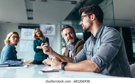 Young designer giving some new ideas about project to his partners in conference room. Business people discussing over new business project in office. - Shutterstock ID 681206938