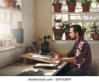 Young designer typing on his laptop while sitting in a creative space that he uses as his office in his studio
