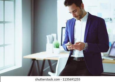 young designer writing sms in his office