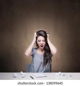 Young desperate girl writing an essay. Conceptual image.