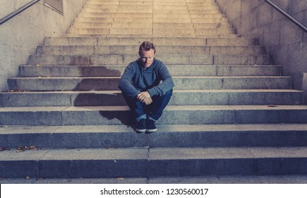 Young desperate jobless man in casual clothes abandoned lost in depression sitting on ground concrete stairs alone in grunge lighting in Emotional pain Loneliness Sadness Mental health concept.