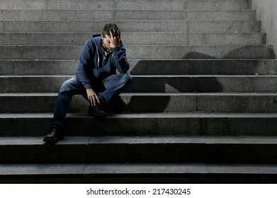 Young desperate man in casual clothes abandoned lost in depression sitting on ground street concrete stairs suffering emotional pain, sadness, looking sick in grunge lighting