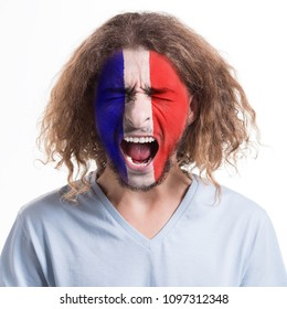 Young desperate man with flag of France painted on face screaming, sad of his favorite football or soccer team losing, sport event, faceart and patriotism concept.