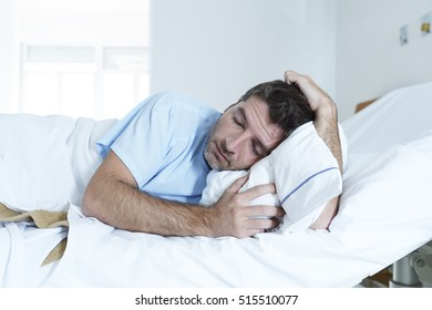 young desperate man lying at hospital bed alone sad and devastated suffering depression crying at clinic for serious disease diagnose feeling worried and in fear about health