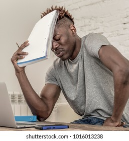 young desperate and overwhelmed black afro American man in stress at home working stressed with laptop computer worried and tired in college university student preparing exam concept
