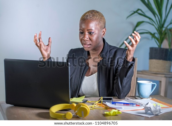 young desperate and stressed african american business woman working at laptop computer desk at office suffering stress feeling sad depressed and overwhelmed in work crisis concept