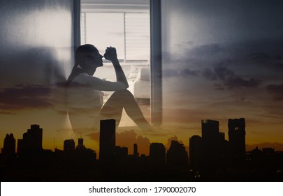 Young desperate woman praying at home against city background.