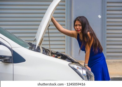 young desperate and worried Asian Korean woman in stress stranded on street roadside with car engine failure having mechanic problem needing repair service feeling helpless and annoyed