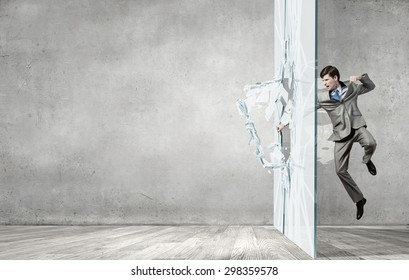 Young determined businessman breaking glass with karate punch