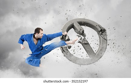 Young determined karate man breaking concrete stop sign