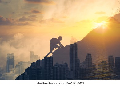 Young determined man climbing up mountain overlooking the city. People, power, challenging yourself, never giving up, and hard work concept. Double exposure
