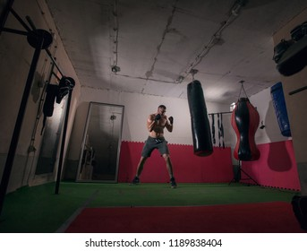 Young determined man exercising boxing in a health club.