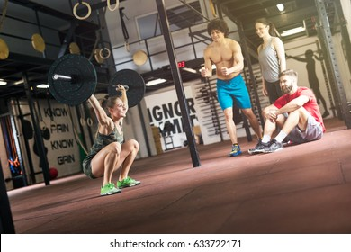 Young determined woman athlete in cross fit gym.