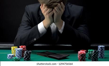 Young devastated businessman losing poker game at casino, gambling addiction
