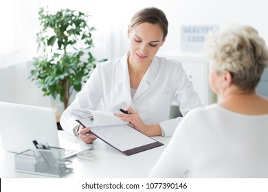 A young dietician sitting in her office and showing an elder woman her diet plan
