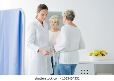 Young dietician taking waist measurements of her senior patient during appointment at a bright office
