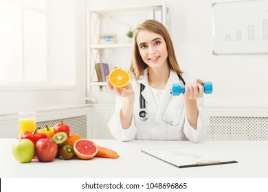 Young dietitian with orange and dumbbell at clinic. Smiling woman nutritionist holding fruit and sport equipment. Weight loss, healthy eating and slimming concept