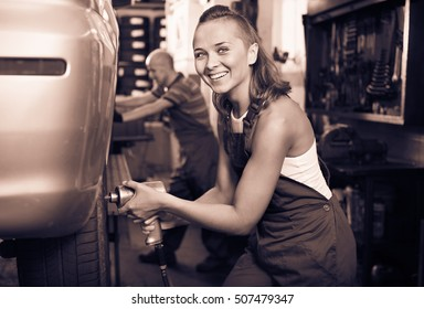 Young diligent smiling  mechanic woman working on wheel equilibrium control machinery in car service