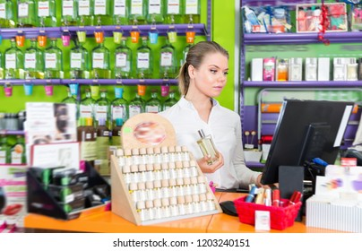 Young diligent  woman perfume seller working on computer in modern perfumery store