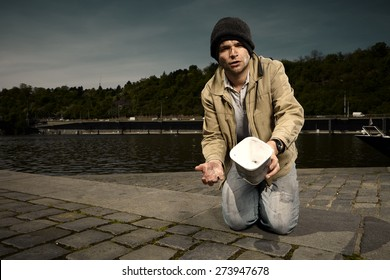 Young and dirty beggar asking for some money on city river bank